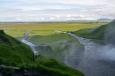 Pohled od vodopádu do dáli, kde se leskne široké řečiště Markarfljótu, odvádějícího vodu z ledovců.