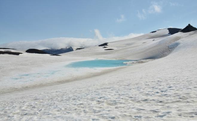 Nezamrzlé tyrkysově modré jezero uprostřed sněhu vypadá dosti neobvykle. Zřejmě se pod ním nachází nějaký ten termální pramen.