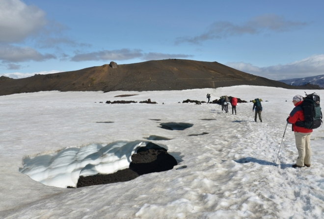 Hned vedle vyšlapané pěšiny zeje asi metr hluboká díra a v ní potok, opět zřejmě z termálního pramene. Vzadu druhý z nových kráterů Móði.