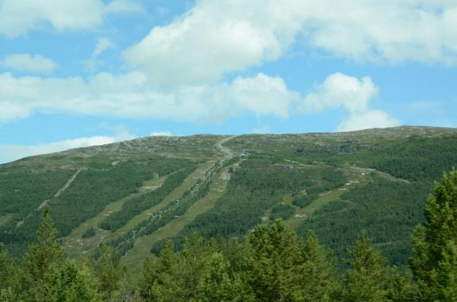 Údolní lesy a poklidná venkovská krajina plynule přecházejí v nehostinnou pustinu na vrcholech, které by výškou zapadly typicky někam do Krkonoš. Cestou potkáváme i lyžařská střediska.