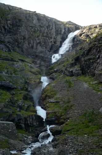 Střihem jsme se přesunuli přímo na Trollstigen, již jsme zahájili výjezd nahoru. První záběr věnujeme vodopádu Stigfossen, vysokému snad 239 metrů. Nepřehlédněte můstek uprostřed fotky.