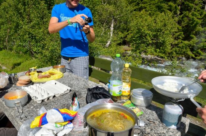 Uprostřed nám již bublá polévka, vlevo v ešusu jsou vajíčka, z kterých Michal za chvíli na pánvi udělá míchaná. Dokonce je na rozdíl od včerejší čočky dobře spočítal. Honza se celým počínáním značně baví a natáčí si ho.