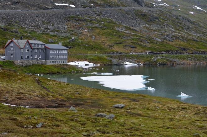 V jezeře plave několik obrovských kusů ledu. V pozadí hotel Djupvasshytta.