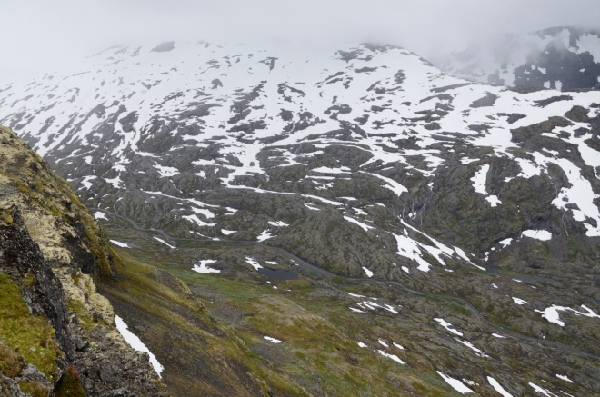 Silnička se zcela ztrácí v mozaice skal, trávy a sněhu