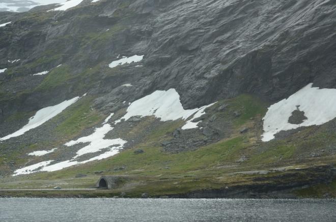 Kousek za jezerem Djupvatnet se nachází jezero Langvatnet, kde uprostřed ničeho ústí tunel vedoucí neznámo kam. My pokračujeme pořád dále bezlesým údolím plným vodních ploch, kde civilizaci připomíná pouze silnice a elektrické vedení.