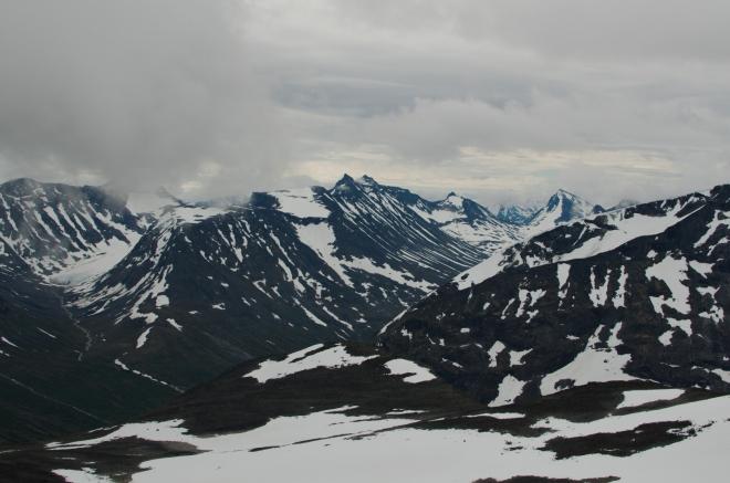 Výhledy na okolní hory se opět trochu proměnily, teď je vidíme pěkně shora. Bohužel se proměňuje i počasí, jak jsme se obávali, a začínají se natahovat mračna.