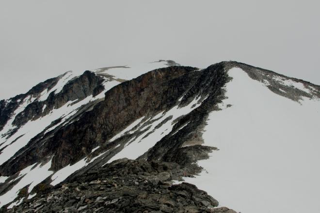 Po zdolání Svellnose je před námi krátké klesání a výstup na další vrcholovou prémii – Keilhaus topp (2355 m n. m.). V pozadí se nám již začíná ukazovat samotný vrchol Galdhøpiggenu. Velké převýšení budilo na papíře respekt, ale zatím ho zvládáme dobře, to nejhorší už máme za sebou.