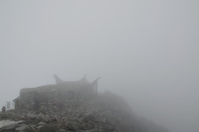 Chata Knut Voles, ve které jsme se před chvílí ohřáli, je z vrcholu přes hustá mračna sotva vidět.
