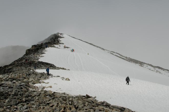 Už jsme zase pod mraky, zahalen je pouze vrchol Galdhøpiggenu. Všimněte si, jak jsou ve sněhu vyježděny koleje od těch, kteří sjíždí z vrcholu po zadku. My se zatím převážně držíme částečného sjíždění svahu vestoje, což funguje rovněž výborně, stačí neztratit rovnováhu.