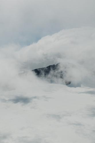 Jeden z blízkých vrcholů v sevření bílých oblak. Na každého nadšeného fotografa tu dnes čeká spousta příležitostí se vyřádit.