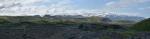 Panorama Eyjafjallajökull. Dole černý písek, v němž se boří naše nohy. Z písku vyčnívají zeleně porostlé kopečky.