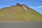 Z šedivé roviny kamenité pouště ční jasně zelené hory.