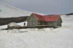 Chata v sedle Hrafntinnusker. Kus pod ní jsou vidět místa na stan obehnaná sněhovou hradbou proti větru.