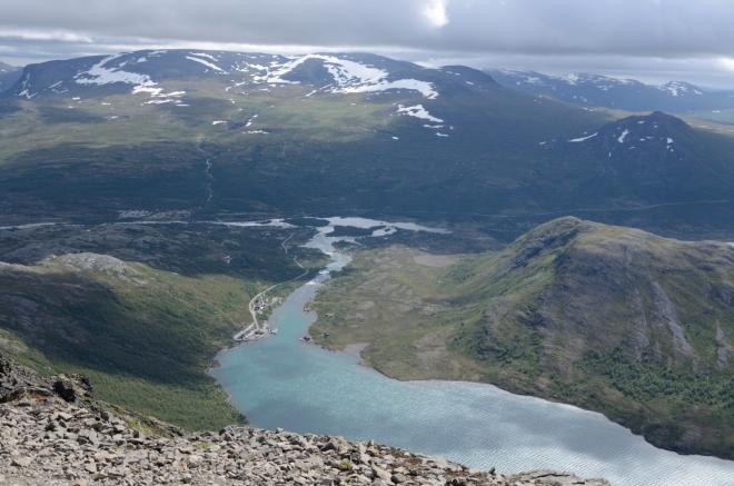 Pohled směrem k parkovišti, v pozadí říčka Sjoa vytékající z jezera. Ta vytváří v členité krajině pohoří Jotunheimen spoustu malých i větších jezírek.