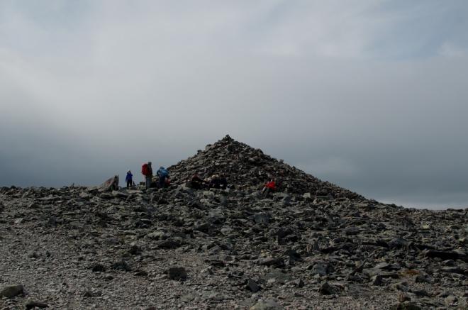 Po asi tři čtvrtě hodině pochodu skoro po rovině se dostáváme na nejvyšší vrchol Besseggenu, Veslfjellet (1743 m). Jeden z důvodů, proč je zde postavena obrovská kamenná mohyla, je nasnadě – jde o významné závětří pro odpočívající turisty.