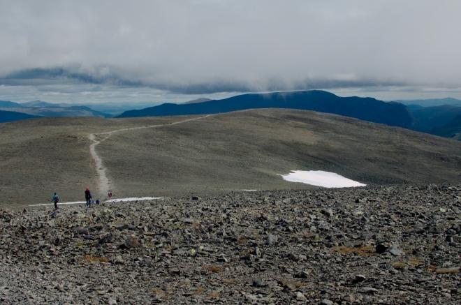 Pohled zpět na kamenitou pláň, po které jsme přišli. V takto otevřeném terénu se člověk nemůže divit tak silnému větru. Horší povětrnostní podmínky než zde jsme možná v Norsku ještě nezažili, člověk sotva dokáže jíž rovně.