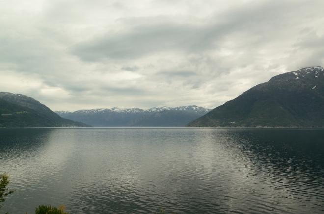 "Silnice při tomto fjordu je nepříjemně úzká, ale výhledy opět parádní, dnes je to opravdu vyhlídková jízda, jak se patří. Na fotce je velká ""křižovatka fjordů"" – místo, kde se Hardangerfjord větví hned do tří koncových ramen. My se stáčíme k tomu nejvýraznějšímu po levé straně, zvanému Sørfjorden (""Jižní fjord"")."