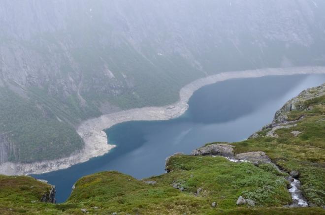 Krásně azurová barva jezera působivě kontrastuje se zelenou trávou.