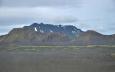 Vnitrozemí Islandu z autobusu cestou do Hrauneyjaru. Kamenitá poušť, občas nějaká zeleň a v dáli vystupující hory.