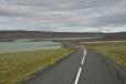 """U Hrauneyjaru ještě chvíli jedeme po asfaltce mezi zelenými loukami a tyrkysovými jezery. Podobně jako tato silnice vypadá většina asfaltek na Islandu včetně okružní """"dálnice"""" Ring road: poměrně úzké, se středovým pruhem, vedoucí bezlesou krajinou mezi pastvinami či loukami."""