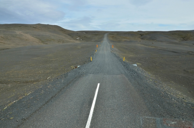 Konec asfaltky a začátek štěrkové cesty, jež se brzy změní na cestu prohrnutou v kamenité poušti.