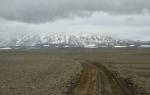 Zatáhlo se, prší a my se blížíme ke krásně zasněženým horám, jejichž vrchní partie pokrývá menší ledovec Tungnafellsjökull. Pod horami leží v Nýidaluru malý kus civilizace (chata).