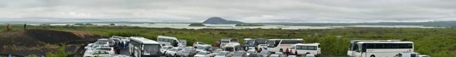 Po příchodu ze skalního města je parkoviště téměř zaplněné. Vzadu jezero Mývatn s pseudokrátery a charakteristickou horou Vindbelgjarfjall.