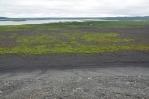 Pohled ze svahu sopky na lávové pole pod ním a Mývatn v dáli.