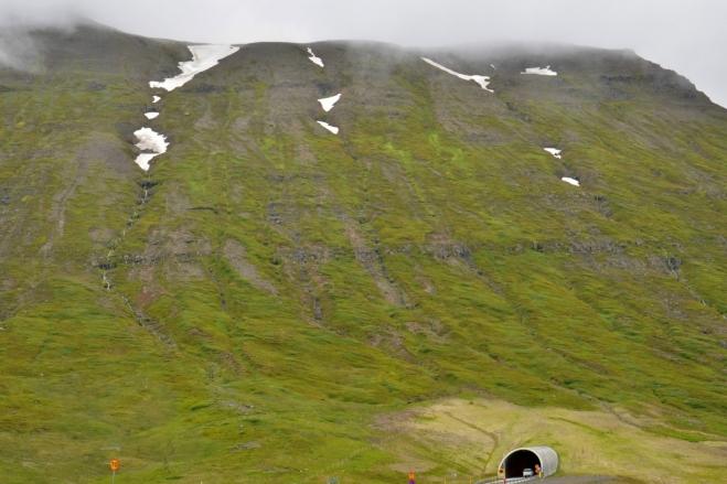 Druhý tunel do Siglufjörðuru a svahy nad ním. Tunely mezi Ólafsfjörðurem a Siglufjörðurem byly postaveny teprve v roce 2010, předtím se mezi těmito městy muselo jezdit přes hory.