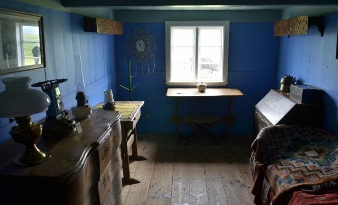 Místnost pro hosty. Vpravo nahoře zdobené prkno, které se dávalo z boku postele, aby netáhlo pod peřinu. Postel měří na délku asi metr nebo jen o málo víc.