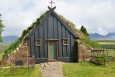 Průčelí kostelíka. Boční zdi tvoří trávové drny.
