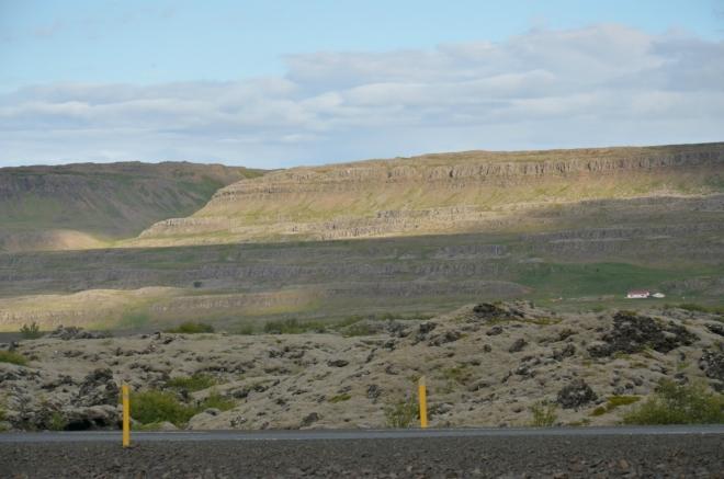 Skály s čedičovými sloupy a lávové pole v popředí