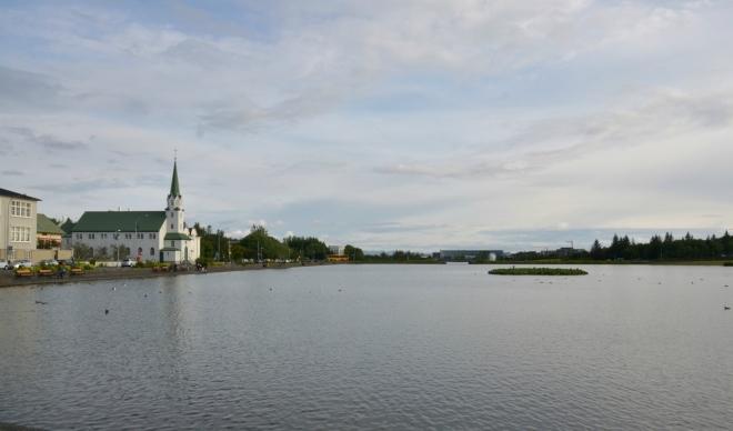 Jezero Tjörnin s kostelem na břehu, focené od radnice