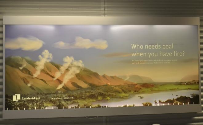 """Plakát na letišti: """"Kdo potřebuje uhlí, když má oheň?"""" Island vskutku produkuje většinu své elektrické energie velmi ekologicky z geotermální energie a ještě ani plně nevyužívá potenciál této """"horké"""" země."""