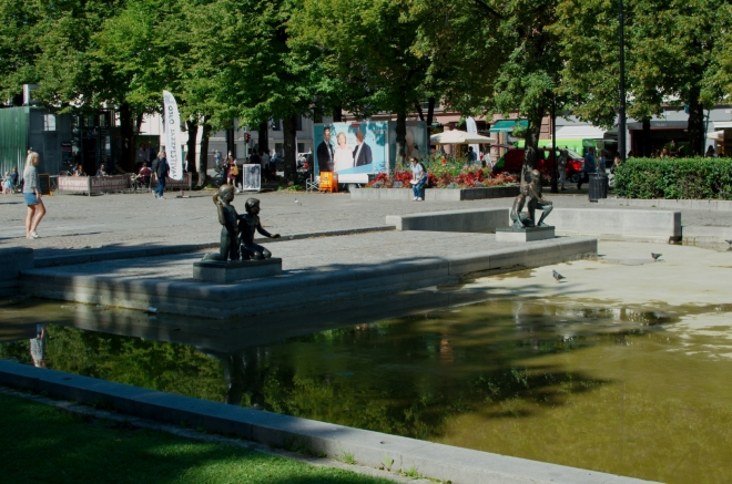Procházíme parkem přilehlým k ulici Karla Johana. Na okraji kašny stojí další sochy, tentokrát jsou na nich vyobrazeny děti.