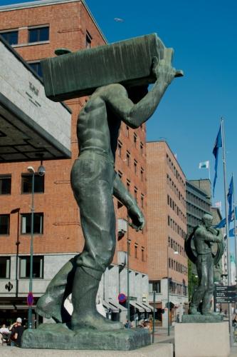 Na samotný závěr jsme si nechali městskou radnici, jsme teď opět kousek od moře. Na fotografii jsou vyobrazeny sochy těžce pracujících Norů, které se nacházejí za budovou, na náměstí přiléhajícím k pobřeží.
