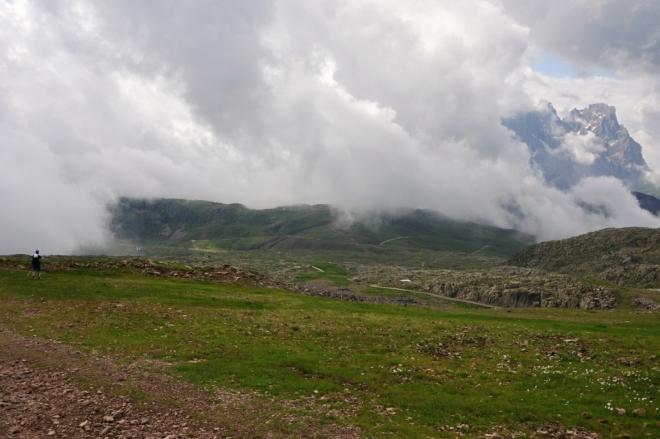Z mlh se vynořují vzdálené vrcholky hor, aby se po chvíli v nich znovu skryly.