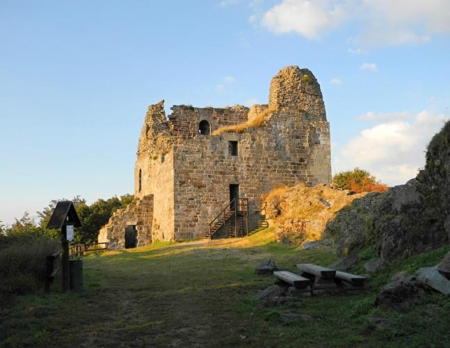 Večerní záříové slunce zbarvuje hradní zdi do zlatova.