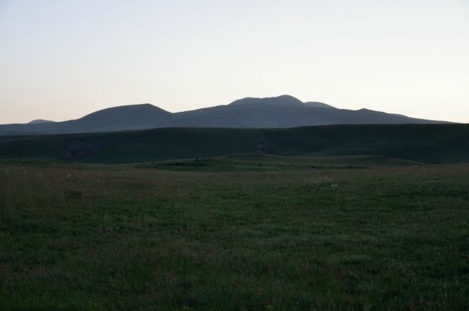 Na horizontu ozářeném vycházejícím sluncem nás vyhlíží vrchol Aždahak, v jehož blízkosti chceme strávit příští noc.