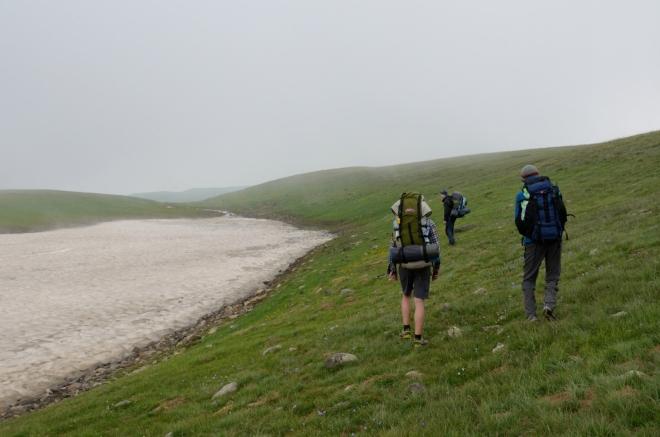 Ani s GPS si nejsme zcela jisti, kudy jdeme. Po půlhodince bloudění však přicházíme k potoku napájenému sněhovým polem, který nám poskytne dostatek vody na vaření. Dokonce se zdá, že mlha už mizí.