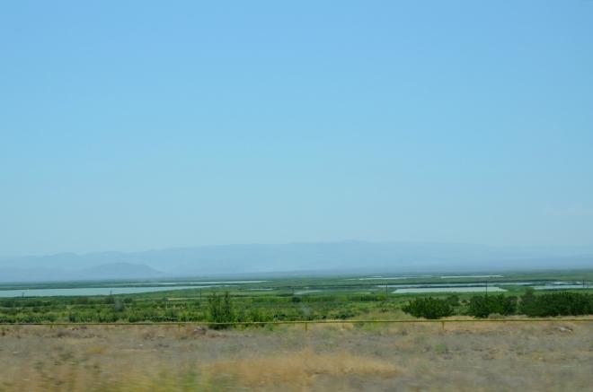 Nacházíme se v oblasti, kde se setkávají hned čtyři země. Zemědělská krajina v popředí je arménská, kopce v pozadí patří Íránu, mezi tím je úzký cíp Turecka. A kdybychom natočili foťák trochu doleva, uvidíme do exklávy Ázerbájdžánu.