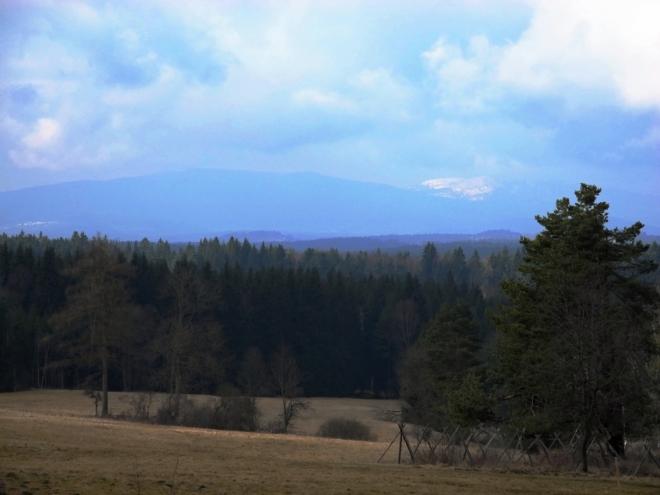 Vzdálená Smrčiná a zřejmě zasněžený vrchol Plechého, nejvyšší hory české strany Šumavy..