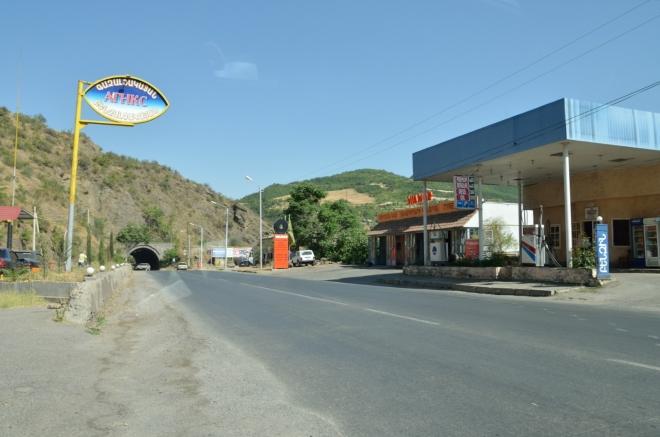 Kapanem, hlavním městem celé provincie s asi 43 tisíci obyvatel, pouze okrajově projíždíme. Fotka zachycuje naše otáčení, neboť jsme přejeli odbočku před tunelem. Za městem opět mohutně stoupáme po hranici, míříme až na jižní konec Arménie.