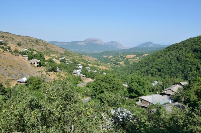 Pauza v zapadlé příhraniční vesničce Čakaten. Odpočíváme ve stínu při zahradách s ovocnými stromy.
