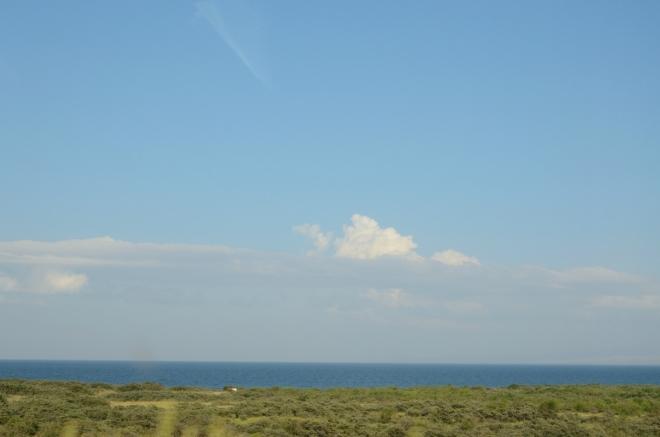 Modrá hladina jezera ve tři čtvrtě na sedm. Objíždíme západní pobřeží.