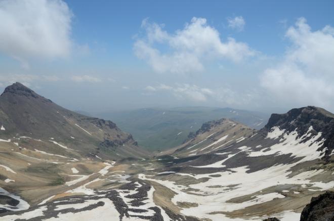Z kráteru vybíhá východním směrem dlouhé údolí až městu Aragats, které se blyští v dálce po levé straně.