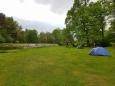 V kempu jsou chatky, kde přebývají cyklisté, louka pro stany je jen pro nás. Moje tropiko ještě nestojí. Teprve večerní déšť mě přinutí ho postavit.