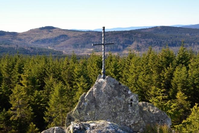 Křížek na skalnatém hřebínku, který umožňuje daleké výhledy.