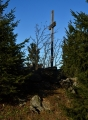 Křížek na vrcholu plochého Poledníku skrývá vegetace.