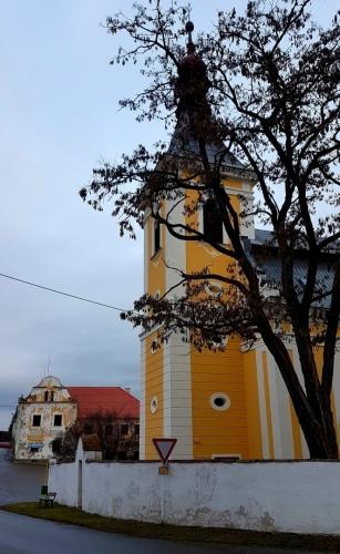 Kostel s domem jihočeského selského baroka.